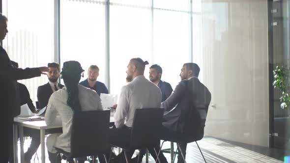 Thumbnail for Multiracial Male Business Executives Discuss Project Sitting at Conference Table