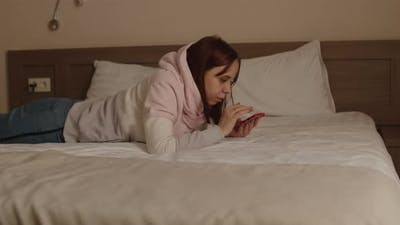 Young Woman Lying on Bed with Mobile Phone