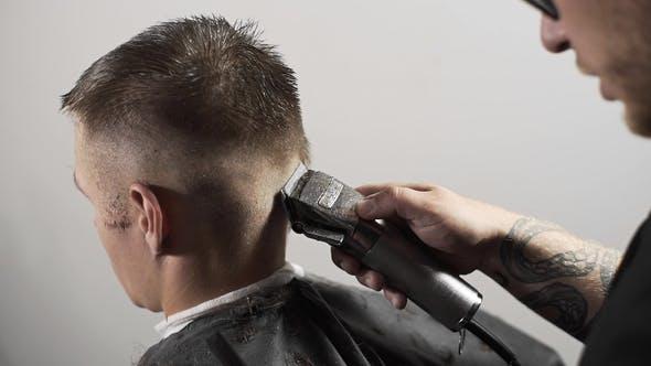 Thumbnail for Tattoed Barber Makes Haircut for Customer at the Barber Shop By Using Hairclipper