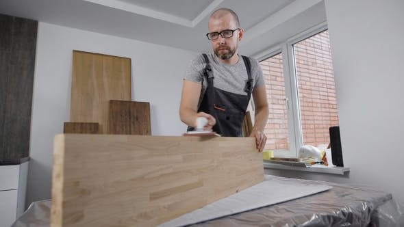 Thumbnail for Professional Carpenter Carefully Working with Sides of Wood Board.