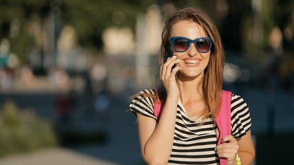 Thumbnail for Woman Talks on Phone in Street
