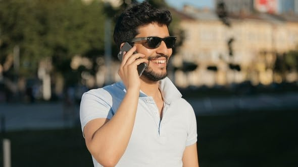 Thumbnail for Man Talks on Phone in Street
