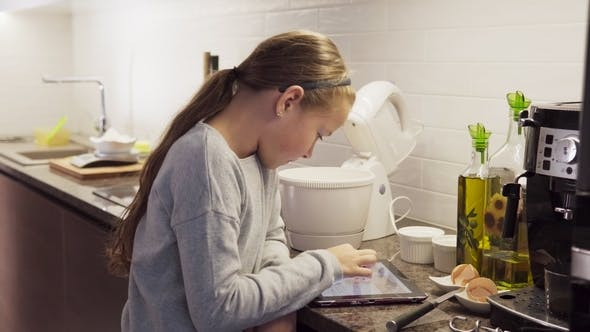 Thumbnail for Little Girl Looking at Food Recipe on Tablet Screen in Kitchen
