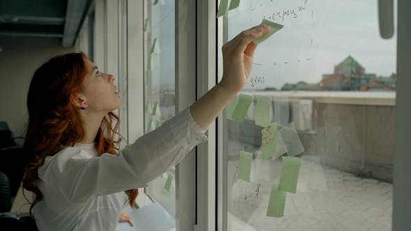 Thumbnail for Beautiful Young Woman Glues Stickers on Window Standing in Modern Office