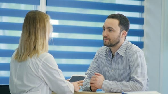 Thumbnail for Male Patient with Sore Throat Getting Doctor Appointment at the Reception