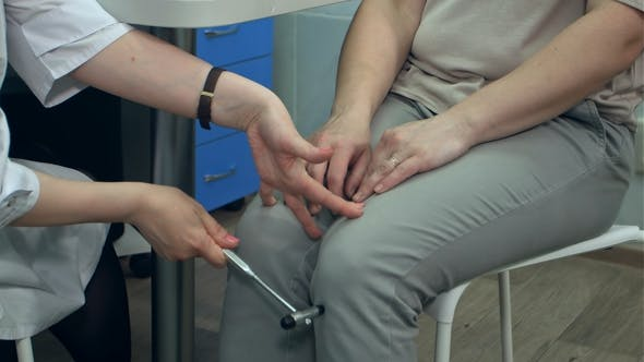 Cover Image for Neurologist Testing Reflexes on Female Patient Using Hammer