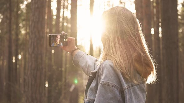Thumbnail for Young Girl Taking Photo at Smartphone in Forest