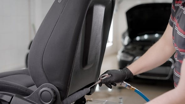 Thumbnail for Man Using High Pressure Spray To Wash the Seat of a Car.