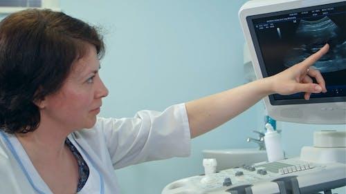Lächelnde weibliche Arzt erklärt Ultraschallergebnisse Blick auf den Bildschirm