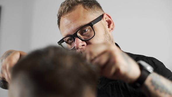 Thumbnail for Tattoed Barber Makes Haircut for Customer at the Barber Shop By Using Scissors and Comb , Man's