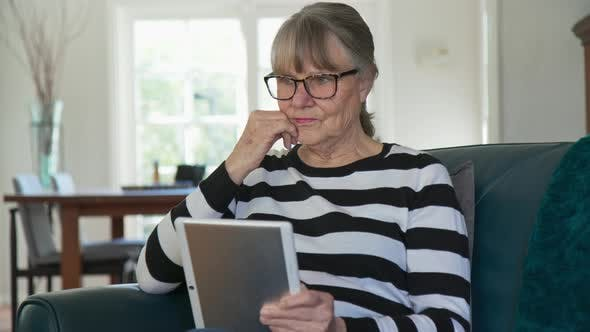 Senior Caucasian woman using tablet computer while sitting in living room