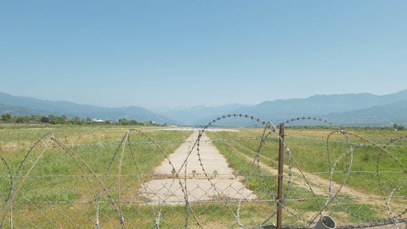 Thumbnail for Walking Along the Barbed Wire Fence of the Airport. Batumi, Geoargia