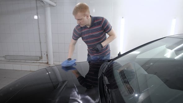 Thumbnail for Male Worker Polishing Black Car Hood with a Dry Towel After Waxing It on a Carwash.