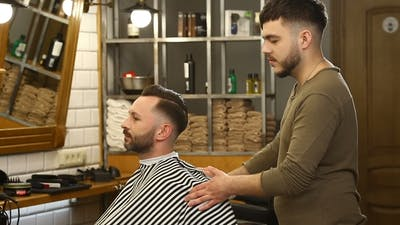 Barber Turns the Client in the Chair at Barber Shop