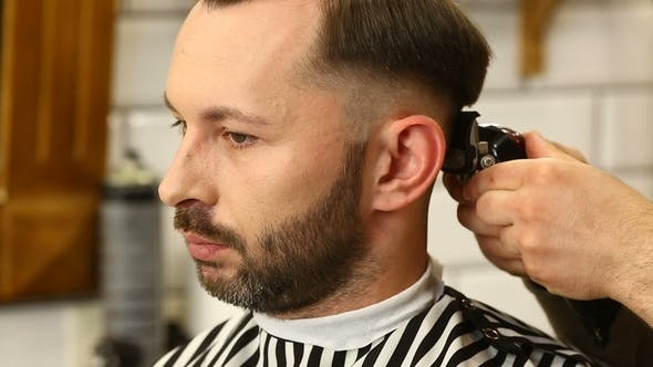 Thumbnail for Barber Trimms Hair of Young Man with Machine