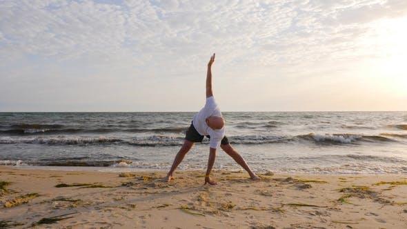 Fitness Man Practising Yoga Asana While Morning Training on Sea Beach
