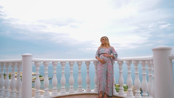 Thumbnail for A Pregnant Girl Stands on the Balcony Next To the Sea and Caresses Her Tummy