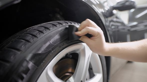 Thumbnail for Shot of a Man Wiping Tire After Cleaning on Car Washing Station.