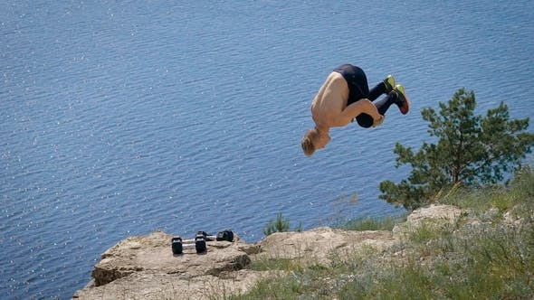 Thumbnail for Muscular Man Doing a Backflip in  on the Hill in Summer.