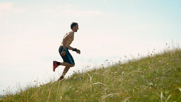 Thumbnail for Side View Shot of a Strong Athletic Man Running Up the Hill.