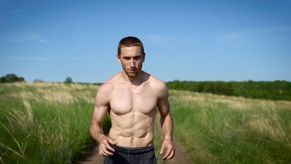 Thumbnail for Portrait of a Muscular Shirtless Man Running Across the Field.