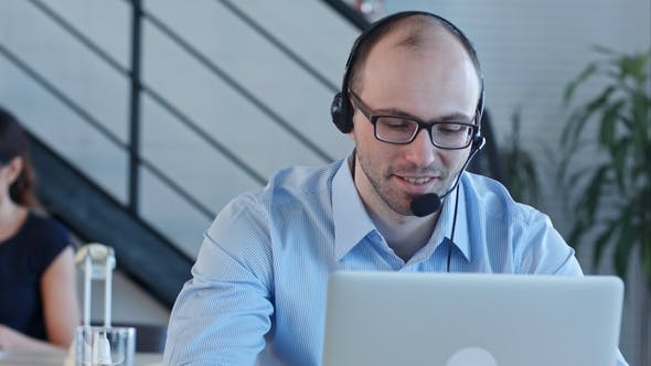 Thumbnail for Joyful Call Centre Agent with His Headset Talking Looking at Laptop