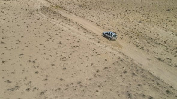 Thumbnail for Suv Car Goes on Sandy Wasteland. Desert Landscape and Lake Shore on Background. Aerial View