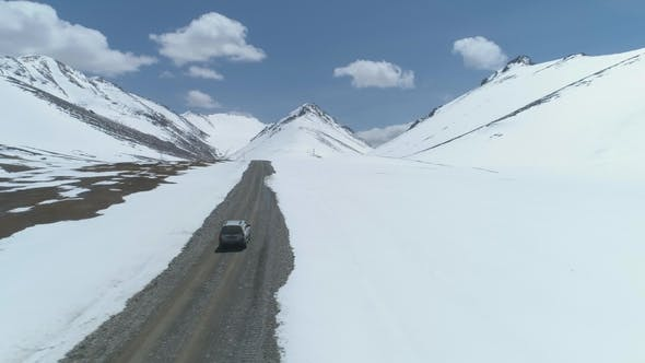 Thumbnail for SUV Vehicle Goes on Road in Snowy Mountains at Sunny Day. Aerial View