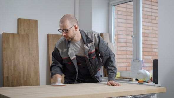 Thumbnail for Adult Bald Worker Man Is Grinding Wooden Board By Hand Sanding Pad in a Workshop in Carpentry