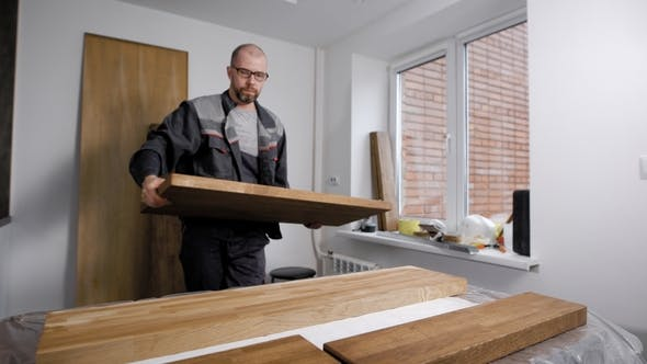 Thumbnail for Woodworker Is Putting Timber Board on a Table in a Workshop of Small Carpentry, Preparing for