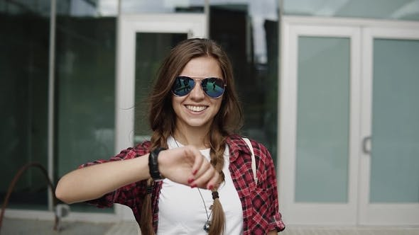 Thumbnail for Cheerful Young Woman with Brown Braided Hair and Modern Glasses and Casual Clothes Looking at Her