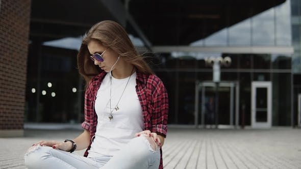 Thumbnail for Attractive Young Woman in Glasses and Casual Clothes Checking the Time on Her Wristwatch Sits on the