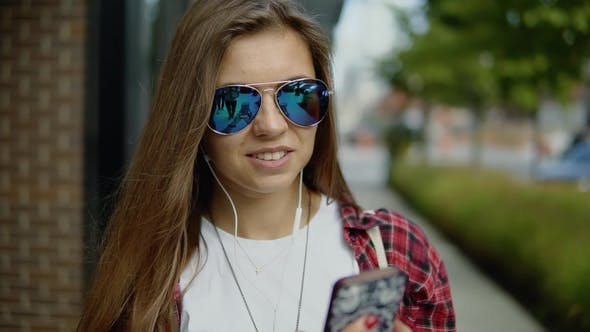 Thumbnail for Cute Young Girl with Long Hair in Glasses Dressed in Casual Clothes Looks on Her Wristwatch Outdoors