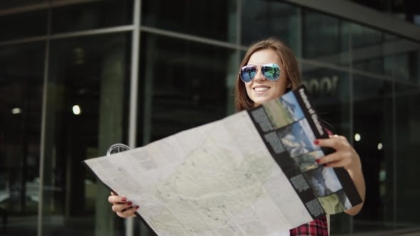 Thumbnail for Pretty 30s Girl Wearing Glasses and Holds Tourist Map Near the Building with Glassy Walls