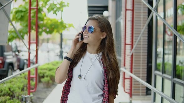 Cover Image for Cheerful Beautiful Woman in Stylish Glasses and Trendy Outfit Has Phone Conversation and Strolling