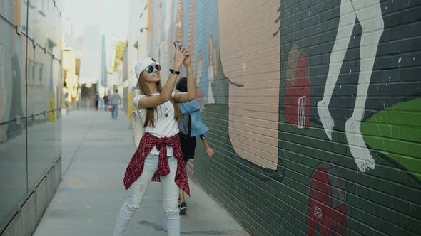 Thumbnail for Cheerful Fashion Woman in Stylish Clothes Taking a Picture on Her Phone the Wonderful Graffiti