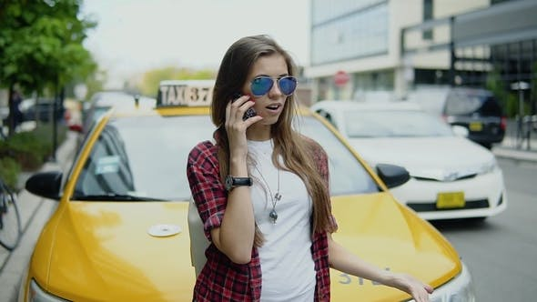 Thumbnail for Attractive Young Woman in Cool Glasses Talking on the Phone Near Taxi Car