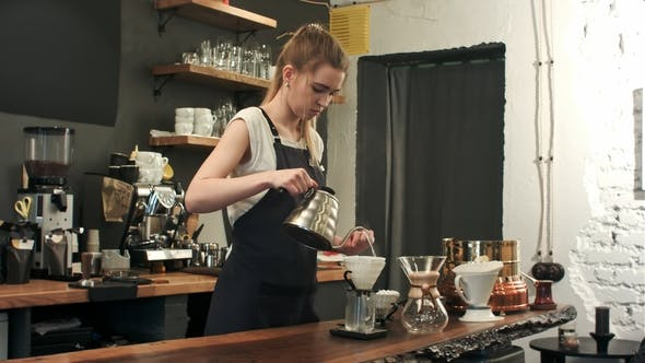 Thumbnail for Young Female Barista in Trendy Modern Cafe Coffee Shop Pours Boiling Water Over Coffee Grounds