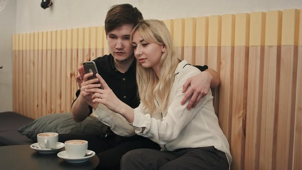 Thumbnail for Happy Couple in a Coffee House Having Breakfast and and Using Cell Phone
