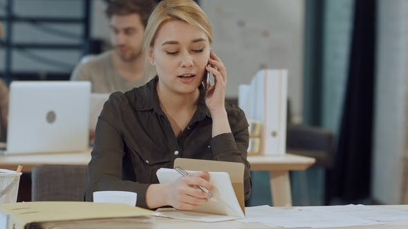Cover Image for Cute Young Female Adult on Phone While Working at Desk