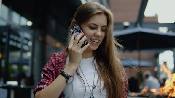 Thumbnail for Cheerful Beautiful Woman in Stylish Glasses and Trendy Outfit Has Phone Conversation and Strolling