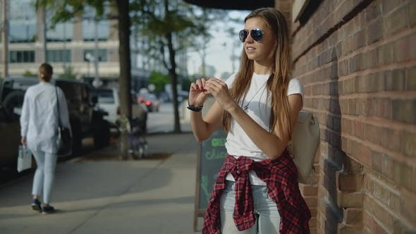 Thumbnail for Lovely Young Girl in Sunglasses Holding an Old Compass in Hands on the Street