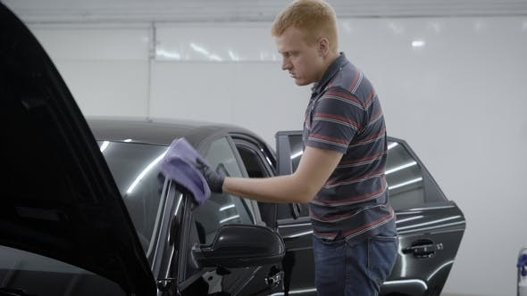 Thumbnail for Washer Is Wiping Cleaned Black Automobile By Soft Cloth After Washing, Polishing It in a Room of Car