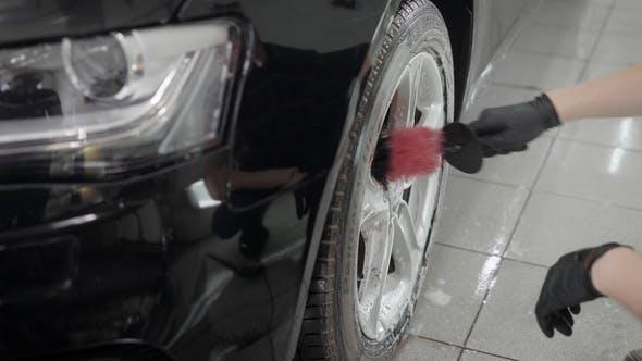 Thumbnail for Arbeiter Man reibt durch Bürste und Seifenschaum ein Rad des Automobils während der Autowäsche, seiner Hände