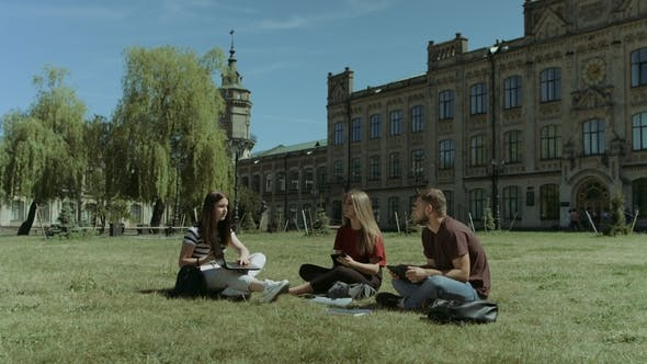 Thumbnail for College Friends Using Electronic Devices on Campus Lawn