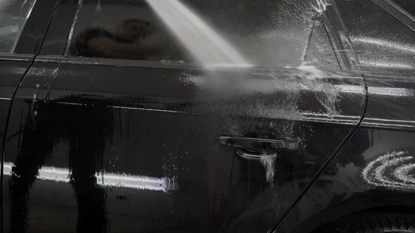 Thumbnail for Man Is Pouring By Water From a Hose Black Automobile in a Garage, Washing Off Soapy Foam From a Body