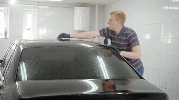 Thumbnail for Young Man Is Rubbing Roof of Black Automobile in a Garage, Washing Car, Wiping Mud on a Surface