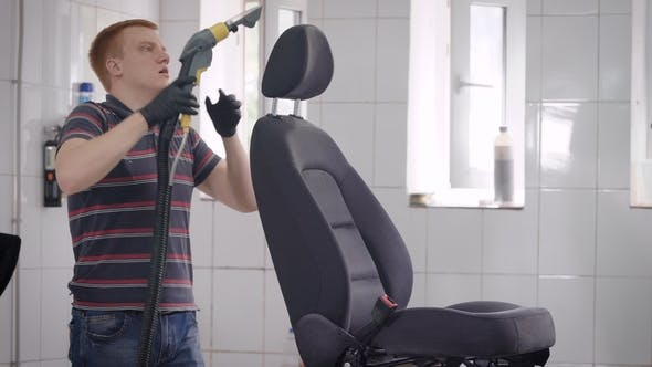 Thumbnail for Car Wash Worker Is Cleaning Seat of Automobile in a Room, Using Vacuum Cleaner, Seat Is Standing on