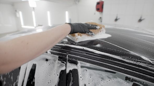 Thumbnail for Washerman Is Rubbing Surface of Black Automobile By Sponge with Soap Foam in Car Washing, Wearing