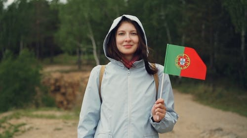 Portrait of Attractive Portuguese Girl Holding Flag of Portugal, Smiling and Looking at Camera